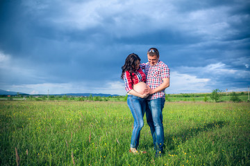 husband and his pregnant wife are walking at sunset in field on