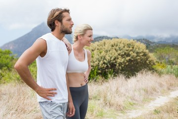 Attractive fit couple standing on mountain trail