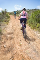 Fit couple cycling up mountain trail on a sunny day