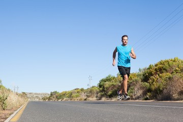 Athletic man jogging on the open road