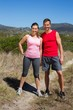 Active couple standing on country terrain smiling at camera