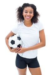 Pretty football player in white holding ball smiling at camera