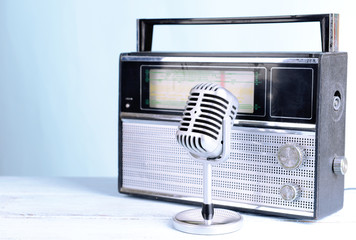 Vintage microphone and radio on table on light blue background