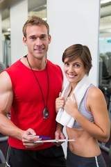 Handsome personal trainer with his client smiling at camera