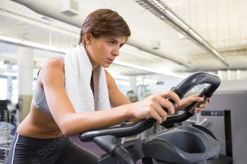 canvas print picture Fit focused brunette working out on the exercise bike