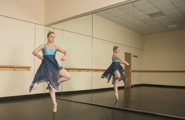 Beautiful ballerina dancing in front of mirror