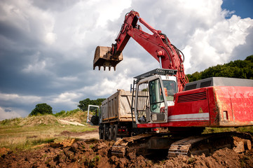 Heavy bulldozer and excavator loading and moving red sand