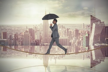 Composite of businessman walking on tightrope holding umbrella