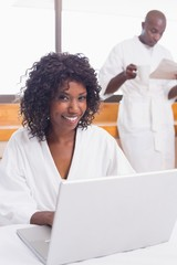 Pretty woman in bathrobe using laptop at table with partner in b