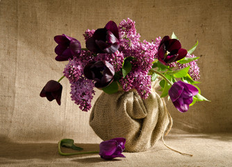 Beautiful bouquet of tulips with sprigs of lilac in a vase on a