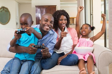 Happy family relaxing on the couch playing video games