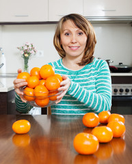Happy  girl holding  heap of mandarins