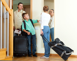 Happy family of three with teenager  with luggage leaving the ho
