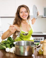 woman in apron cooking  soup in kitchen