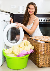 Nice woman washing clothes in washer