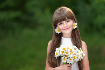 portrait of a beautiful little girl with chamomile