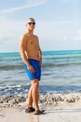 Man in blue swim shorts in the beach