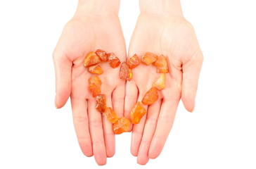 Raw amber shaped heart on hand of woman