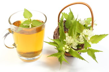Fresh nettle in wicker basket and cup of beverage