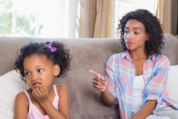 Pretty mother sitting on couch scolding petulant daughter