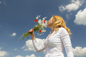 Woman smelling flowers with blue sky in the background