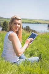 Pretty blonde sitting on grass using her tablet smiling at camer
