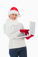 Festive woman using laptop smiling at camera