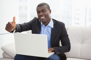 Happy businessman sitting on couch with laptop showing thumbs up