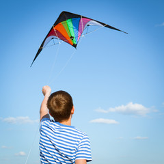 boy flies kite into blue sky