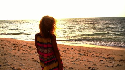 Young Woman Walking on Beach under Sunset Light. Slow Motion.