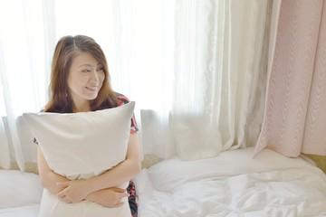 ベッドの上で枕を抱いてくつろぐ日本人女性