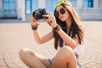 A girl takes pictures the old camera on city streets.