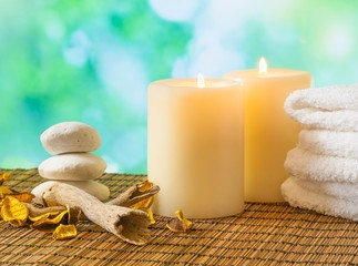 Spa massage with towel stacked, candles and stone