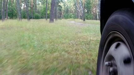 POV camera shot driving at country road with wheel visible.