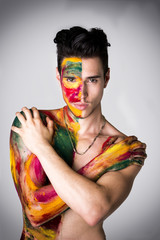 Attractive young man shirtless, skin painted with colors