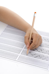 Child hand filling out multiple choice test with pencil