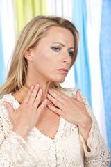 Frau tastet Schilddrüse ab