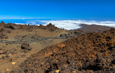 Path in the Teide between volcanic rocks and a ocean of clouds