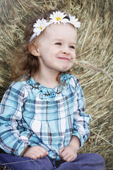 Little girl sitting by the hay bale