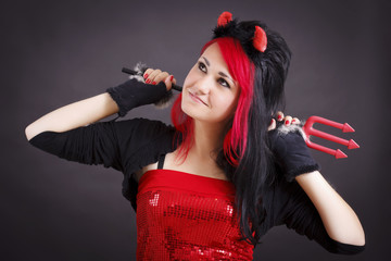 Beautiful young woman in devil costume