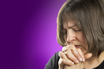 Mature woman in fervent prayer on violet background
