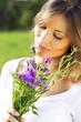 Junge Frau mit lila Blumenstrauß