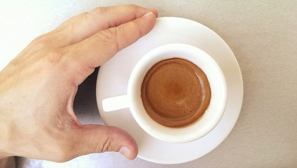 Small white cup of strong black espresso coffee and male hand