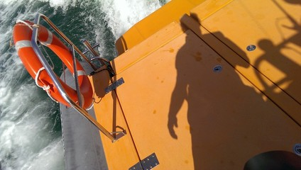 Fast trip on the rescue boat, safety ring buoy and man shadow