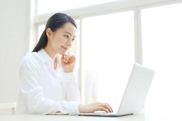 ノートパソコンの前で悩む若い女性
