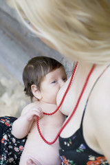 close up portrait of baby breastfeeding