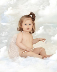 Baby dressed as an angel sits on the cloud