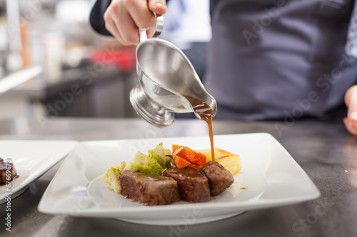 Fotobehang Koken Chef plating up food in a restaurant