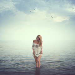 Beautiful girl in the water. Beach, sunrise, cold morning.