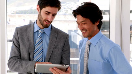 Businessman using tablet pc with his colleague
